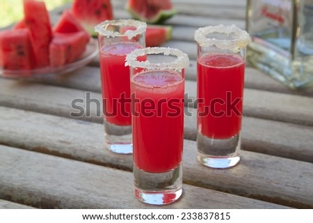 Watermelon cocktail with vodka in small glasses on an old wooden surface. A bottle of vodka and pieces of fresh watermelon in the background - stock photo