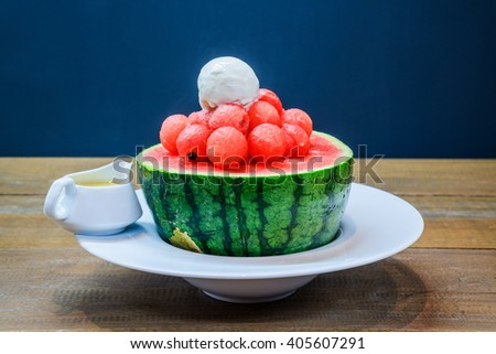 Watermelon granita and icecream in watermelon with sweetened Condensed Milk on wooden table. - stock photo
