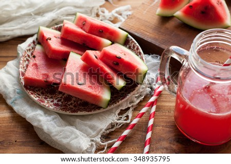 Watermelon Juice in a Mason Jar with Paper straws and Melon pieces cut in the background on a wooden surface  - stock photo