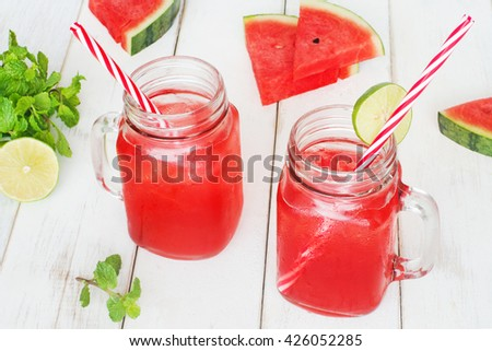 Watermelon lemonade / watermelon cocktail in mason jar with red striped straw,  watermelon slices, mint and lime on a wooden white table. Selective focus. - stock photo