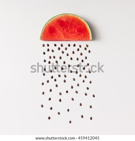 Watermelon slice with seeds raining. Flat lay. Weather concept.