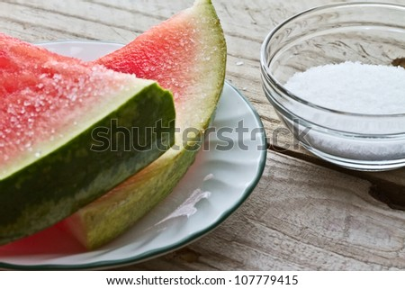 Watermelon slices and salt on picnic table - stock photo