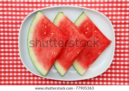 Watermelon Slices on dish on red and white checkered background - stock photo