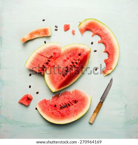 watermelon slices with knife on blue wooden background, top view - stock photo