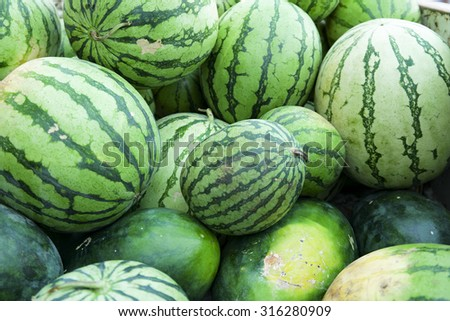 Watermelons. Fresh watermelons on display in a sunday market. Selective focus with shallow depth of field. - stock photo