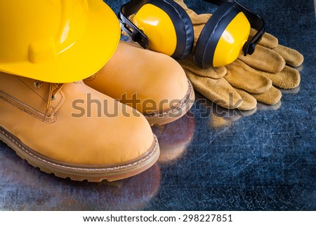 Waterproof boots leather protective gloves earmuffs and building helmet on scratched metallic background construction concept. - stock photo
