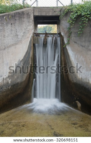 Waters streams over the spillway of a small concrete dam that blocks Hartman Creek and forms a small lake. - stock photo