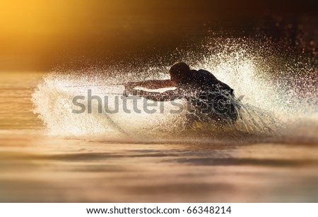 Waterskier silhouette moving fast in splashes of water at sunset - stock photo
