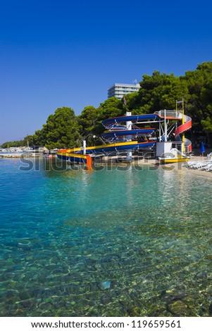 Waterslide and catamaran on beach - vacations background - stock photo