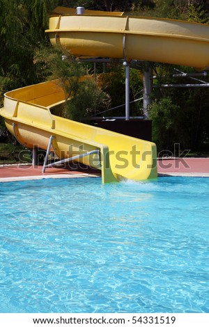 Waterslide of yellow colour in an aquapark - stock photo
