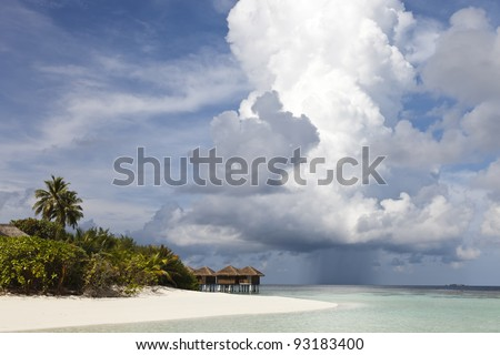 watervillas of paradise island front a cloudy sky and rain on blue lagoon and ocean - stock photo