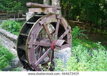 waterwheel / A mill a spinning in the country landscape.