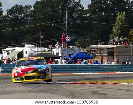 WATKINS GLEN, NY - AUG 11, 2013:  Kyle Busch (18) wins the Cheez-It 355 at The Glen race at the Watkins Glen International in Watkins Glen, NY on Aug 11, 2013. - stock photo