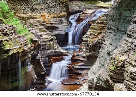 Watkins Glen waterfall in woods with rocks and stream in Watkins Glen state park in New York State - stock photo