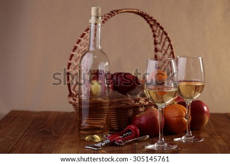 Wattled basket with burlap full of fresh ripe red apples and orange with glassy bottle and two goblets with white wine and corkscrew standing on wooden table top on paper background - stock photo