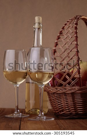 Wattled basket with burlap full of fresh ripe red apples with glassy bottle and two goblets with white wine standing on wooden table top on paper background, vertical picture - stock photo