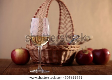 Wattled basket with fresh ripe red apples and glassy bottle with one goblet with white wine in foreground standing on wooden table top on paper background, horizontal picture - stock photo
