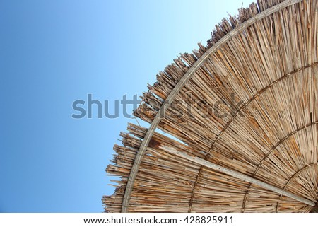 Wattled straw beach umbrella on clear blue sky background. Outdoors summertime multi colored closeup image. View from below. Horizontal. - stock photo