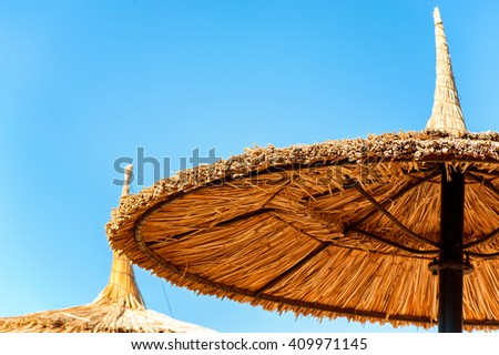 Wattled straw beach umbrellas on clear blue sky background. Outdoors summertime multi colored closeup horizontal image. View from below. - stock photo