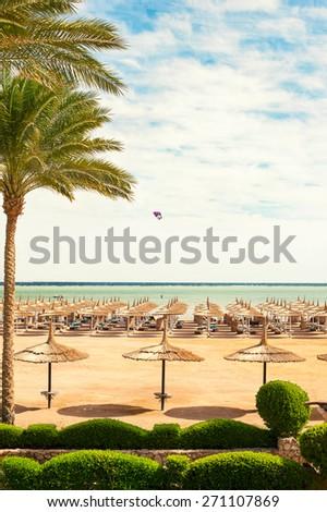 Wattled straw umbrellas on sunny summer beach. Egypt. Sharm-el-sheikh. Outdoors. - stock photo