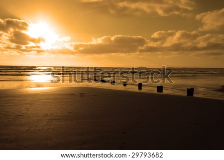 wave breakers at sunset on a golden beach in youghal county cork ireland