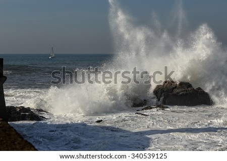 Wave breaking against the rocks near of the harbor entrance of the Douro river mouth, Porto, Portugal - stock photo