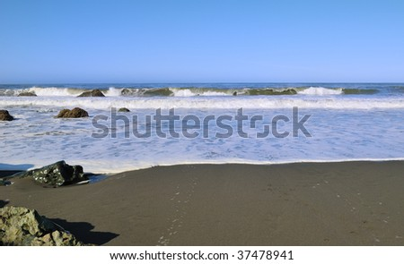 Wave breaking at the beach - stock photo