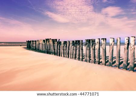 wave-breaking wooden poles, on the beach, tilt-shift effect - stock photo