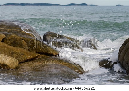 Wave crashing on rock beach
