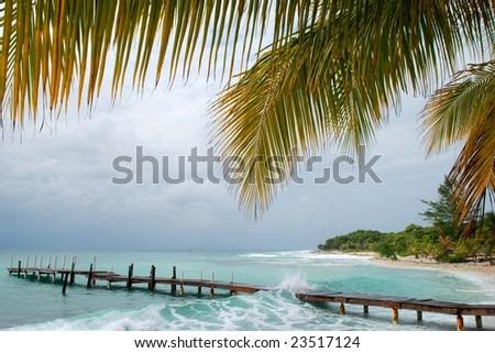 Wave crashing over pier;  Utila, Bay Islands, Honduras - stock photo