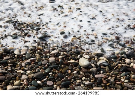 Wave is transformed into foam on a pebble beach in Cyprus. Shallow depth of field. - stock photo