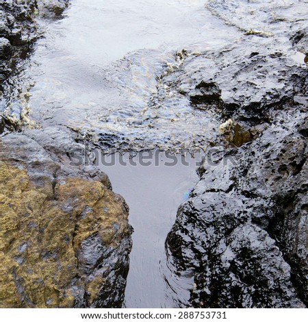 wave of crude oil spill and seawater on the stone at the beach - stock photo