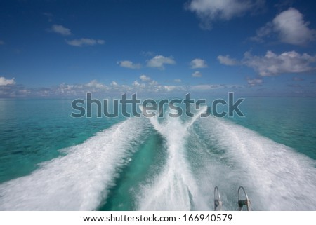 Wave of power boat creates long white wave pattern in turquoise blue tropical waters