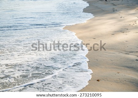 Wave of the sea on the sand beach - selective focus - stock photo
