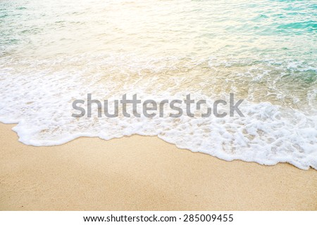 Wave of the sea on the sand beach with sunlight , for background - stock photo