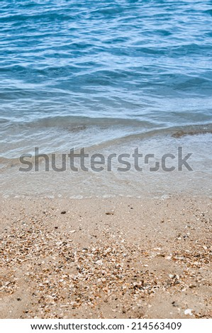 Wave of the sea on the sandy beach - stock photo