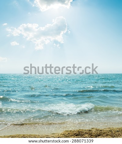 wave on sea and blue sky with clouds and sun - stock photo