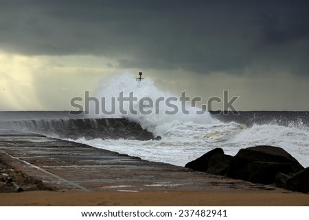 Wave over pier and beacon of Ave river mouth, north of Portugal, before rain and big storm - stock photo