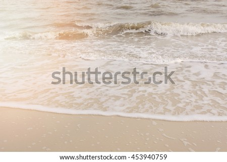 Wave ripples on a sandy beach shore, with applied filters and sun glow. - stock photo
