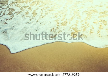 Wave sea water on the beach - vintage effect style and sun flare filter processing style pictures - stock photo