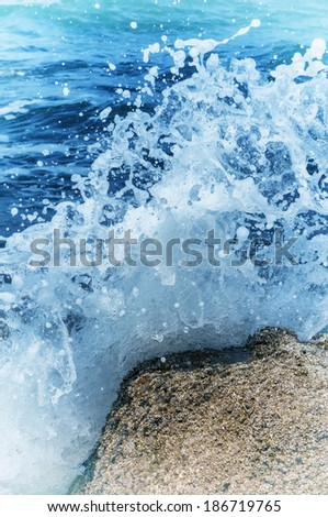 Wave splash against coastal rock - stock photo