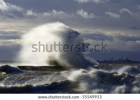 Wave splash at the pier on a stormy day - stock photo