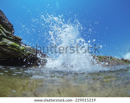 wave splash in the ocean against beach rocks - stock photo