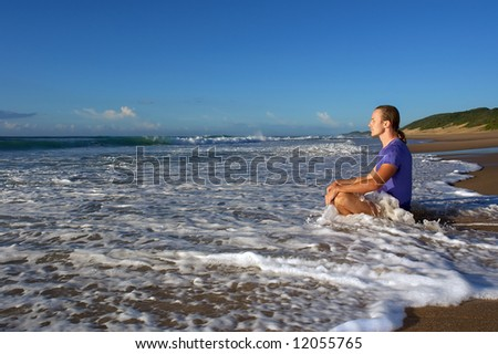 Wave splashes on meditating young man. Shot in Sodwana Bay Nature Reserve, KwaZulu-Natal province, Southern Mozambique area, South Africa.