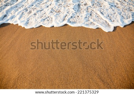 Wave washing up onto a sea shore in the evening light - stock photo