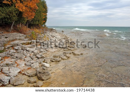 Waves along the rocky coast of Lake Michigan, Door County in the Autumn. - stock photo
