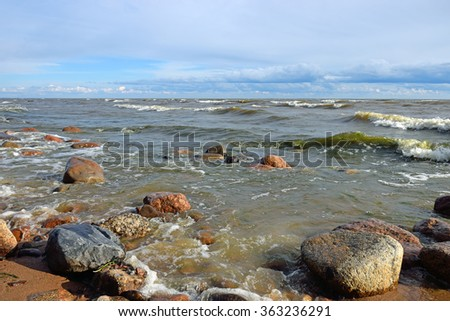 Waves and coastal surf on the sandy beach of the Gulf of Finland at sunset on a Sunny summer day