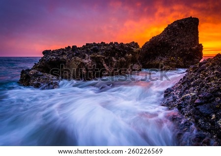 Waves and rocks in the Pacific Ocean at sunset, at Woods Cove, in Laguna Beach, California.