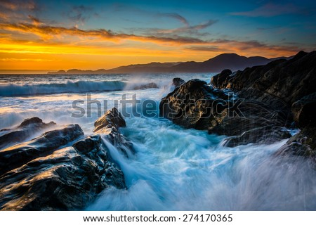 Waves and rocks in the San Francisco Bay at sunset, seen from Baker Beach, San Francisco, California. - stock photo