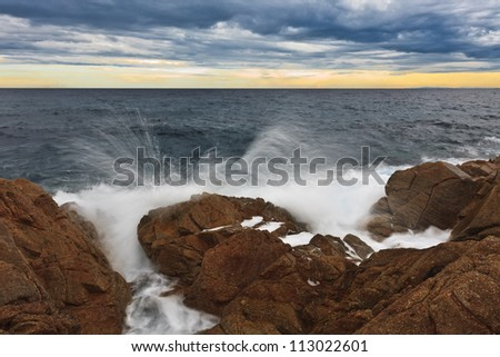 waves and rocks on a wild beach - stock photo